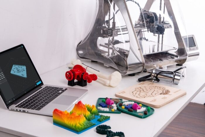 A bunch of 3D printed prototypes and a laptop next to a 3D printer