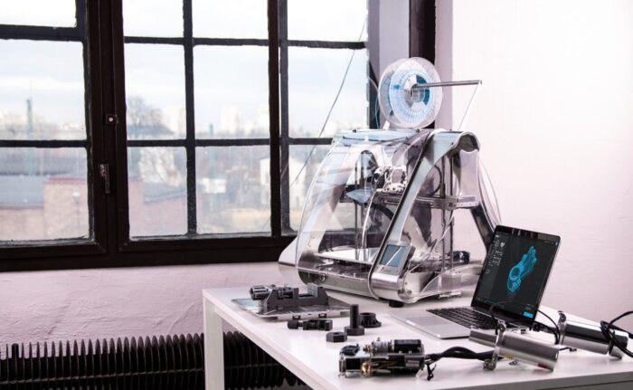 A 3D printer next to a laptop and some prototypes