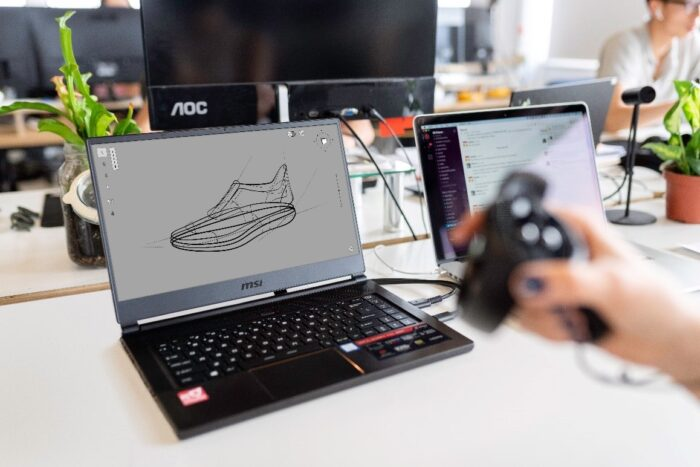 A design engineering working on a blueprint of a shoe