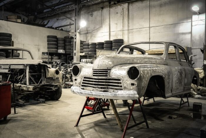 An Old-Timey Car Minus Chassis and Tires, Held Up with Iron Stands In A Restoration Shop