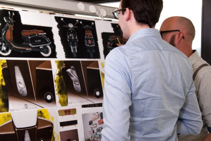 Men looking at scooter designs for a prototype
